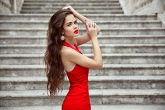 Beautiful brunette girl in red dress with long healthy hair posi Royalty Free Stock Photos