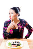 Beautiful brunette girl with red lips funny holding chopsticks and tasting sushi looking at camera on white background portrait Royalty Free Stock Photo