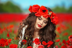 Beautiful brunette girl in red poppy flowers field nature backgr Royalty Free Stock Photography