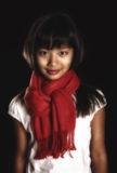 Beautiful brunette girl in a red scarf around his neck. On a black background. Girl with Asian appearance Royalty Free Stock Images