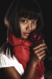 Beautiful brunette girl in a red scarf around his neck, with a red rose in her hand. On a black background. Girl - Korean woman Stock Photography