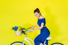 Beautiful brunette girl riding bicycle on blue. And yellow background royalty free stock images