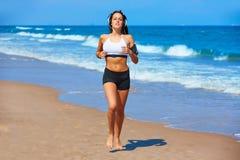 Beautiful brunette girl running in a summer beach Stock Photo
