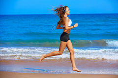 Beautiful brunette girl running in a summer beach Stock Images