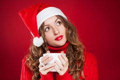 Beautiful brunette girl in Santa Clause hat holding white mug Stock Image