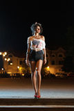 Beautiful brunette girl shot at night. In down town wearing short jeans and american flag t-shirt Stock Photos