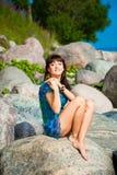 Beautiful brunette girl sitting on beach stones. Portrait of beautiful slim brunette girl enjoying sunlight against sea landscape sitting on beach stones in Stock Photography