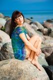Beautiful brunette girl sitting on beach stones. Portrait of beautiful slim brunette girl enjoying sunlight against sea landscape sitting on beach stones in Royalty Free Stock Photos