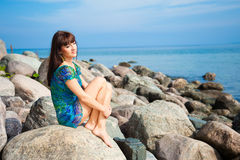 Beautiful brunette girl sitting on beach stones. Portrait of beautiful slim brunette girl enjoying sunlight against sea landscape sitting on beach stones in Stock Photos