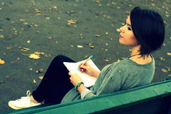 Beautiful brunette girl sitting on the bench and writing into a diary Royalty Free Stock Image