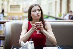 Beautiful brunette girl sitting in a coffee shop Royalty Free Stock Photo