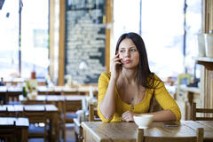 Beautiful brunette girl sitting in a coffee shop Royalty Free Stock Photography