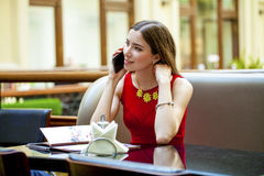 Beautiful brunette girl sitting in a coffee shop Royalty Free Stock Photos