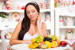 Beautiful brunette girl sitting at the kitchen table with a plate of fresh fruit. Stock Images