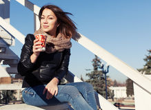 Beautiful brunette girl sitting on stairs on a sunny day with a glass in his hand. Close up. Outdoor Stock Images