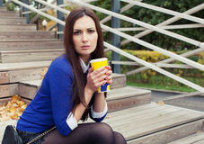 Beautiful brunette girl sitting on wooden steps with a glass and looking at the camera Royalty Free Stock Photos