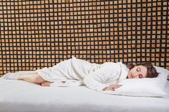 Beautiful brunette girl sleeping on a white bed Stock Images