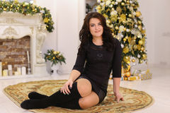 Beautiful brunette girl smiles and posing while sitting on backg royalty free stock images