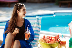 Beautiful brunette girl smiling, drinking cocktail, sitting near swimming pool. royalty free stock images