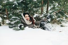 Beautiful brunette girl smiling, lying in the snow. In winter cl