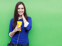 Beautiful brunette girl standing with a glass in his hand near the green wall and smiling at the camera stock images