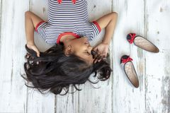 Beautiful brunette girl with striped dress next to her slippers royalty free stock images
