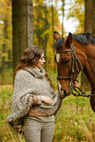 Beautiful brunette girl stroking a horse in an autumn forest.  Stock Images