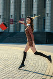 Beautiful brunette girl in stylish dress jumps on the city squar Stock Image