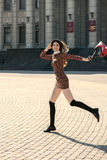 Beautiful brunette girl in stylish dress jumps on the city squar Royalty Free Stock Image