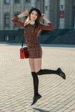 Beautiful brunette girl in stylish dress posing on the city squa Stock Photography