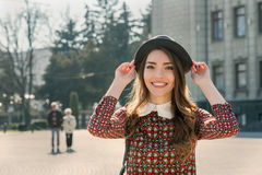 Beautiful brunette girl in stylish dress posing on the city squa Royalty Free Stock Images