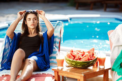 Beautiful brunette girl sunbathing, lying on chaise near swimming pool. Copy space royalty free stock photos