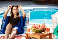 Beautiful brunette girl sunbathing, lying on chaise near swimming pool. Royalty Free Stock Photos
