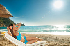 Beautiful brunette girl sunbathing on a sunbed  at  the sea Royalty Free Stock Image