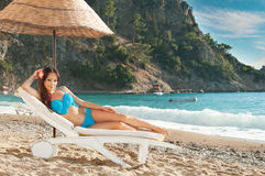 Beautiful brunette girl sunbathing on a sunbed  at  the sea Stock Images