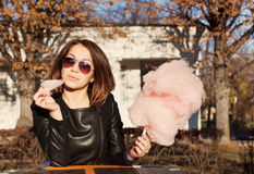 Beautiful brunette girl in sunglasses eating candy floss at a table in summer cafe Stock Photo
