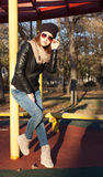 Beautiful brunette girl in sunglasses posing near pillar sunny autumn evening in cap, black jacket and blue jeans Stock Photography
