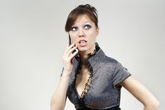 Beautiful brunette girl talking on the phone. On a background Royalty Free Stock Photos
