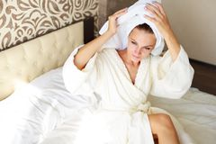 Beautiful brunette girl with a towel on her head in bed. She was taking a shower royalty free stock photo