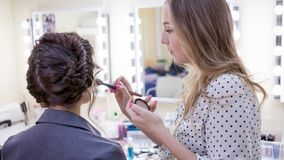 Beautiful brunette girl uses the services of a professional makeup artist. Beauty shop. Make-up artist and her client stock photo