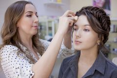 Beautiful brunette girl uses the services of a professional makeup artist. Beauty shop. Make-up artist and her client royalty free stock photo