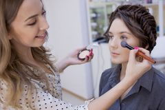 Beautiful brunette girl uses the services of a professional makeup artist. Beauty shop. Make-up artist and her client stock photos