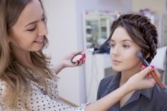 Beautiful brunette girl uses the services of a professional makeup artist. Beauty shop. Make-up artist and her client royalty free stock photography