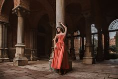 Beautiful brunette girl, with very long hair, in an orange, vintage dress royalty free stock photo