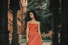 Beautiful brunette girl, with very long hair, in an orange, vintage dress stock photo