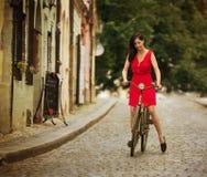Beautiful brunette girl on a vintage bike Stock Images