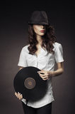 Beautiful brunette girl with vinyls on dark background Stock Images