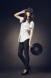 Beautiful brunette girl with vinyls on dark background Royalty Free Stock Photo