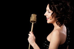 Beautiful brunette girl vocalist singing with smile holding gold stock photography
