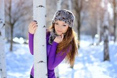 Beautiful brunette girl on a walk in the winter near the birch Stock Photos